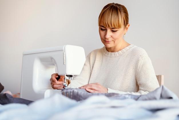 Op maat vrouw met behulp van naaimachine