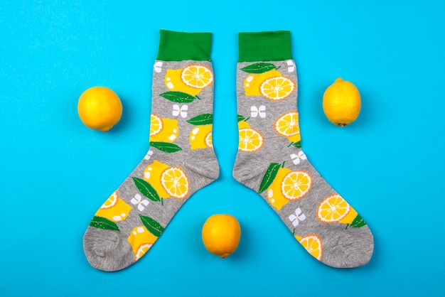 Op mening over kleurrijk paar sokken en citroenenvruchten die op blauwe oppervlakte worden geïsoleerd
