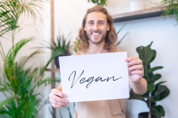 Op mijn manier. witte poster met woord vegan in uitgestrekte armen van gelukkige jonge bebaarde man die binnenshuis staat