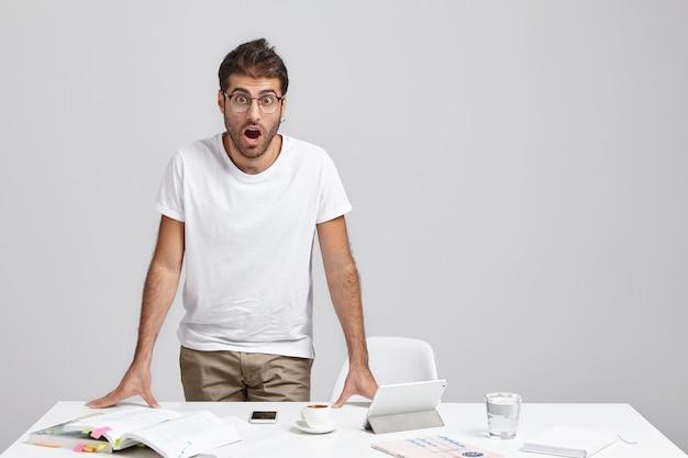 Op nee. portret van aantrekkelijke bug eyed bebaarde donkerharige mannelijke werknemer permanent aan zijn bureau
