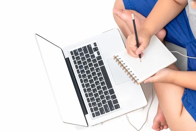 Op notitieboekje schrijven en jongen die online bestuderen