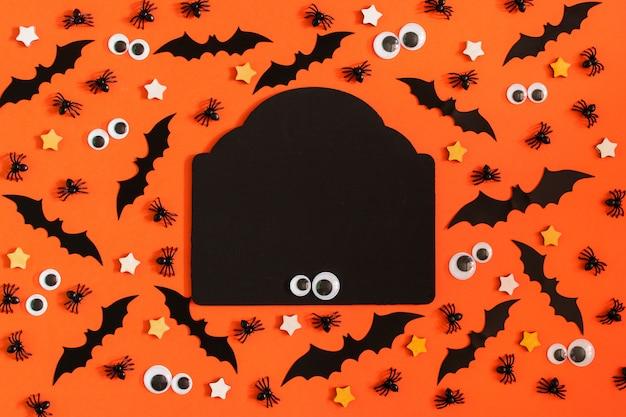 Op oranje achtergrond zijn bekleed met veel decoratieve vleermuizen, sterretjes en marionettenogen.