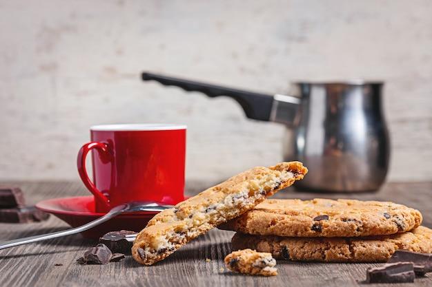 Op oude houten tafel, koffie in rode kop, koekjes, chocolade en turkse koffiepot.