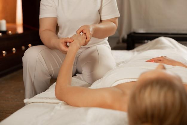 Op overdekt bed. nauwkeurige masseuse in wit kostuum gericht op handen tijdens complexe massagesessie