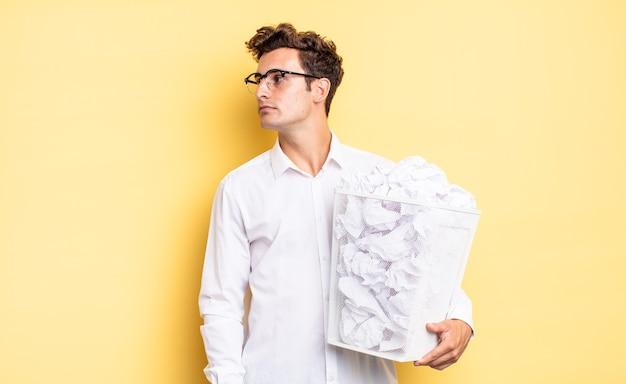Op profielweergave kijkend om de ruimte vooruit te kopiëren, denken, fantaseren of dagdromen. prullenbak papier concept