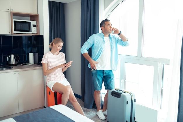 Op reis gaan. getrouwd stel klaar om op vakantie te gaan op zoek naar een taxi naar het vliegveld, zittend op hun ingepakte reisgerei.