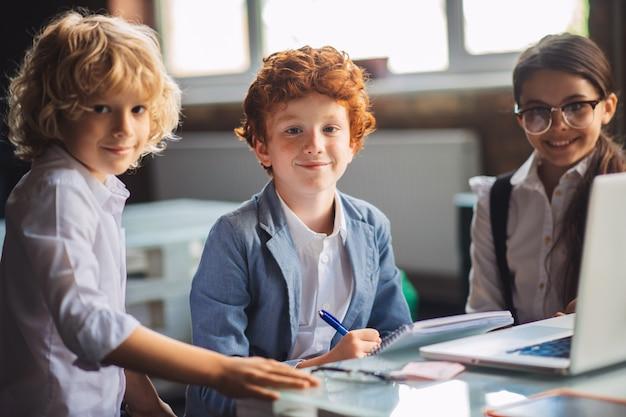 Op school. drie schattige kinderen studeren in de klas en kijken gelukkig