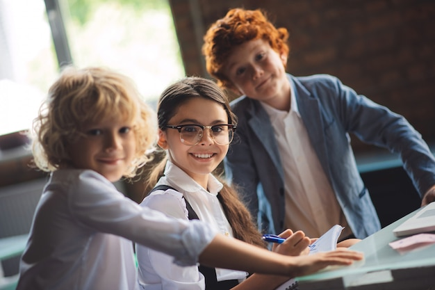 Op school. drie schattige kinderen studeren in de klas en voelen zich opgewonden