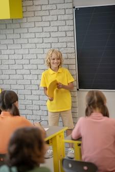 Op school. een jongen in gele t-shirt die zich bij het bord bevindt