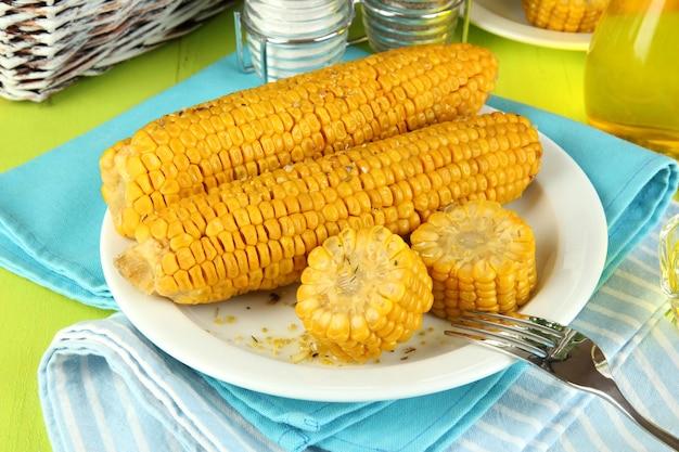 Op smaak gebrachte gekookte maïs op plaat op houten lijstclose-up