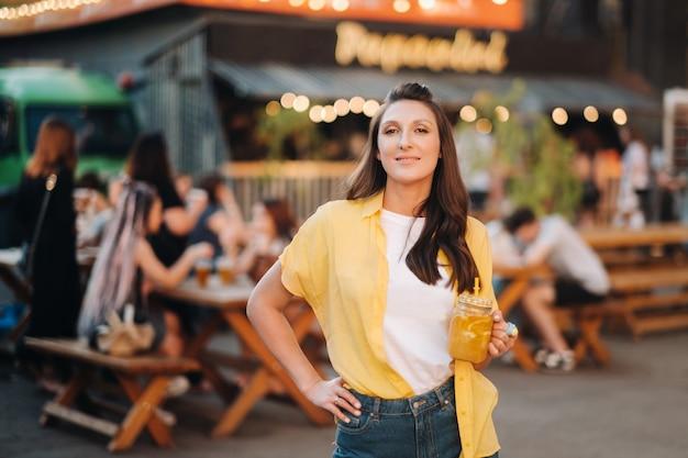 Op straat staat een meisje in een geel shirt en korte broek met een glas citroensap.