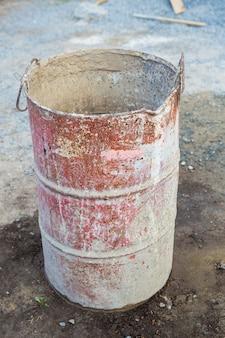 Op straat staat een oud roestig metalen vat bedekt met veelkleurige vlekken. alles voor reparatie, constructie.