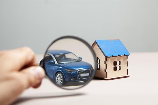 Op tafel een auto, een huis en een vergrootglas. huis en auto zoekconcept