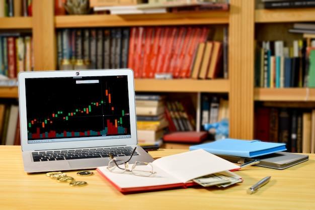 Op tafel gouden bitcoins, notebook, eyeglases en laptop met beursgrafiek op scherm