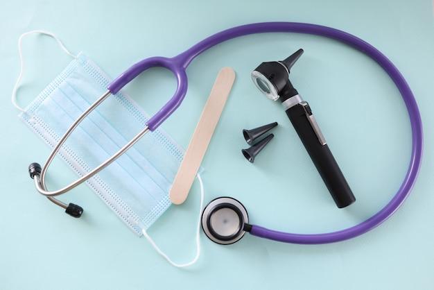 Op tafel is beschermend otoscoopmasker en keelplank. medische instrumenten voor otolaryngoloog concept