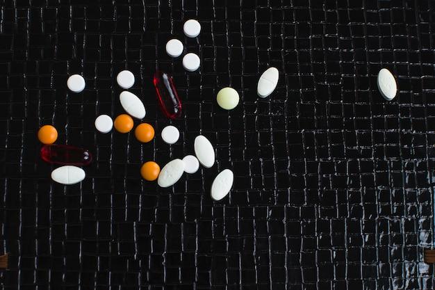 Op tafel liggen ampullen, daarna verschillende pillen, medicijnen en medicijnen