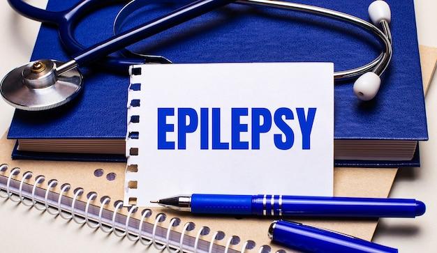 Op tafel liggen blocnotes, een stethoscoop, een pen en een vel papier met de teksten epilepsy. medisch concept