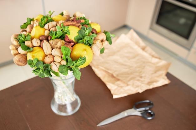 Op tafel liggen een mooi fruitboeket en gesneden inpakpapier om in te pakken