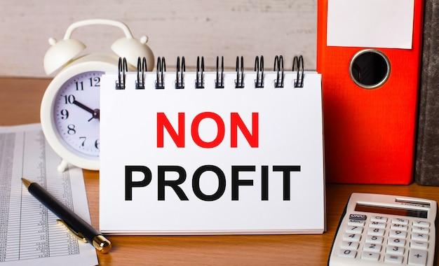 Op tafel liggen rapporten, een witte wekker, een rekenmachine, mappen voor papieren, een pen en een wit notitieboekje met de non profit. bedrijfsconcept