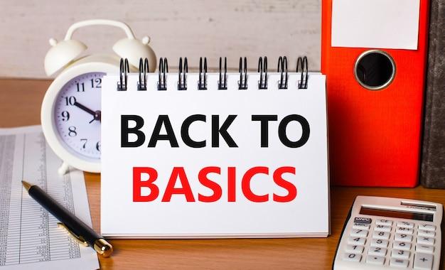 Op tafel liggen rapporten, een witte wekker, een rekenmachine, mappen voor papieren, een pen en een wit notitieboekje met de tekst back to basics. bedrijfsconcept