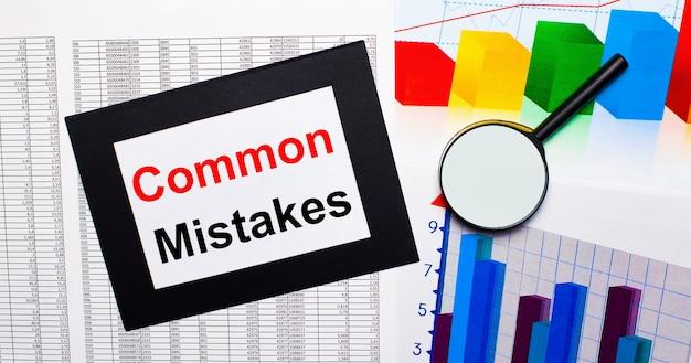 Op tafel liggen verslagen van veelkleurige kaarten, een vergrootglas en een vel papier in een zwarte lijst met de tekst common fouten. bedrijfsconcept