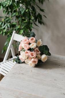 Op tafel ligt een delicaat boeket rozen. op tafel liggen decoratieve bloemen.