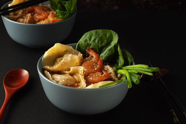 Op tafel staat een kom noedelsoep met garnalen, wontons en spinazie