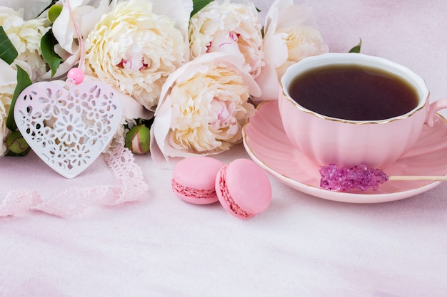 Op tafel staat een kopje thee, suiker, bitterkoekjes, hart en roze kant en witte pioenrozen