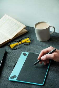 Op tafel staat een laptop, grafisch tablet en een kopje koffie. kantoor artikelen. werkomgeving. uitzicht van boven. donkere houten achtergrond.