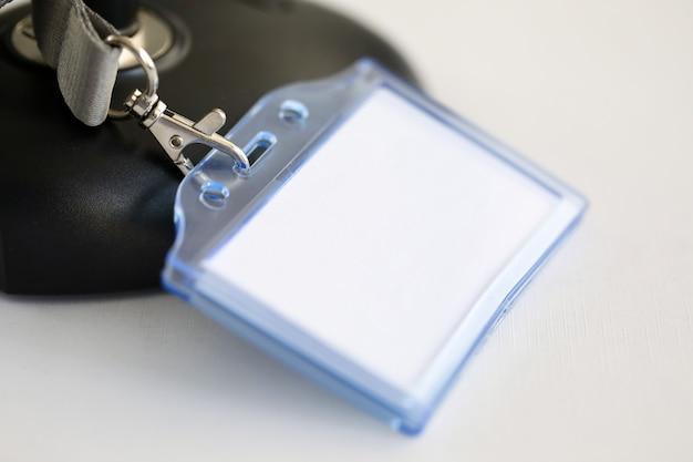 Op tafel staat plastic plaquette, een lege badge
