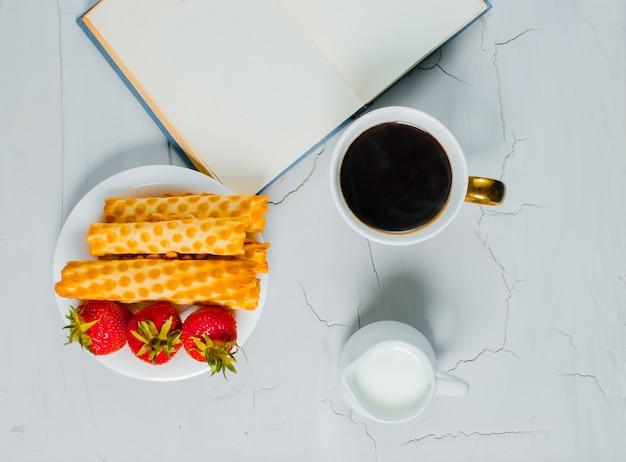 Op tafel staat warme koffie, room en een zoet dessert met verse aardbeien
