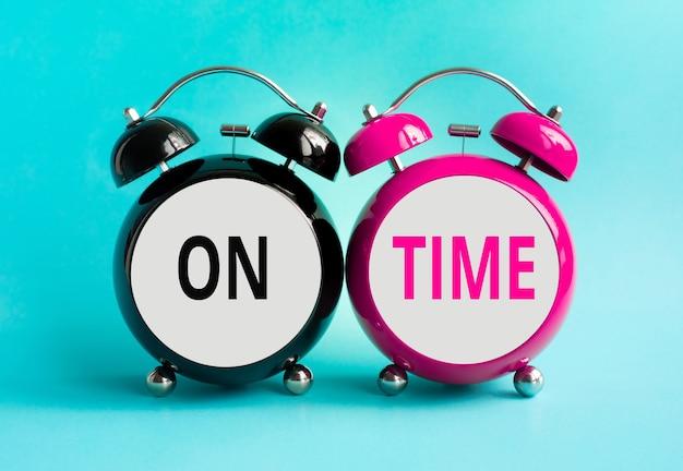 Op tijd concepten met tekst op voorzijde van wekker op kleurrijke achtergrond. zakelijke prestaties. tijd en deadline