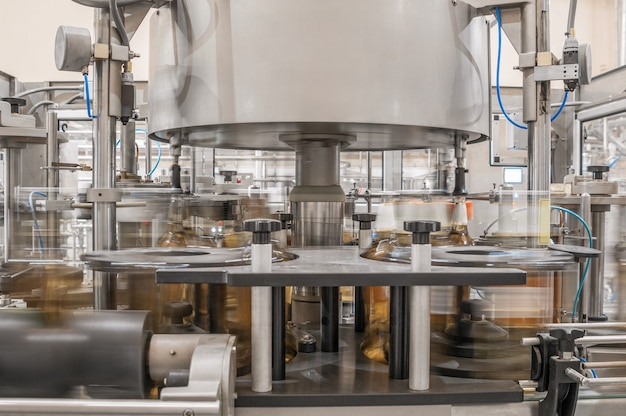 Op transportband drankjes in flessen vullen fabriekswinkel voor de productie van glazen flessen