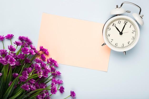 Op weergave bloemen met kaart en klok naast