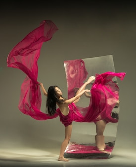 Op weg naar ideaal. moderne balletdanser op bruine muur met spiegel. illusie reflecties op het oppervlak. magie van flexibiliteit, beweging met stof. concept van creatieve kunst dansen, actie, inspirerend.
