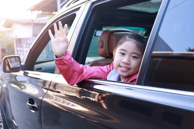 Op weg naar school stak het kleine meisje lachend en glimlachend zijn hand uit het autoraam.
