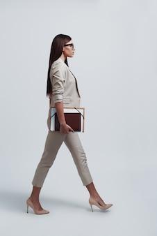 Op weg naar zakelijke bijeenkomst. volledige lengte van aantrekkelijke jonge vrouw die een dossier draagt terwijl ze tegen een grijze achtergrond loopt