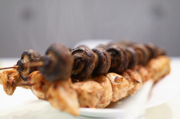 Op wit bord zijn kebab vlees en champignons
