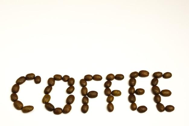 Op witte lege achtergrond koffiebonen aangelegd woord coffee