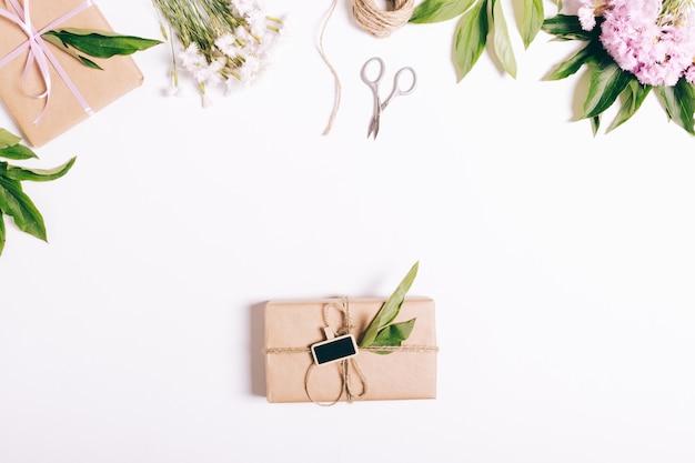 Op witte tafel liggen dozen met geschenken, bloemen, linten en andere versieringen
