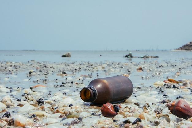 Op zee worden glazen flessen weggegooid, garbage ligt op het strand
