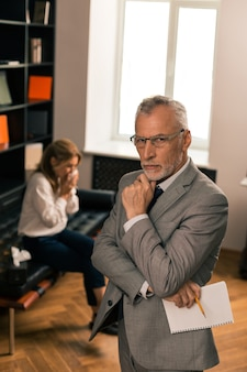 Op zoek naar antwoorden. ernstige psycholoog die in zijn kantoor staat en naast zijn huilende vrouwelijke patiënt denkt