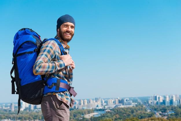 Op zoek naar avonturen. knappe jonge man die rugzak draagt en camera door de schouders kijkt met een glimlach