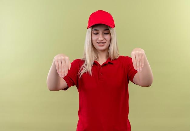 Op zoek naar beneden levering jong meisje dragen rode t-shirt en pet in tandsteun tonen neem gebaar op geïsoleerde groene achtergrond