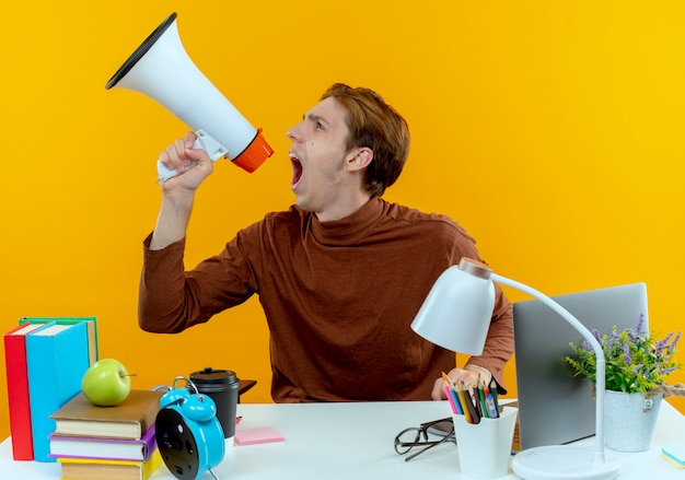 Op zoek naar boze jonge student jongen zit aan bureau met hulpmiddelen van de school spreekt op luidspreker