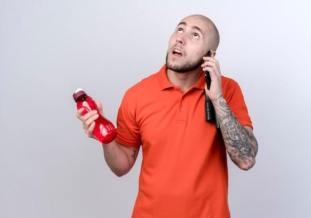Op zoek naar denken jonge sportieve man waterfles te houden en spreekt over de telefoon