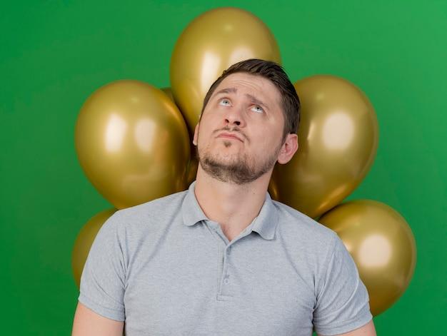 Op zoek naar doordachte jonge partij man grijs shirt dragen staande voor ballonnen geïsoleerd op groen kijken