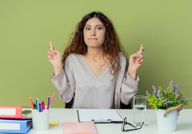Op zoek naar een bezorgde jonge, mooie vrouwelijke kantoormedewerker die aan een bureau zit?