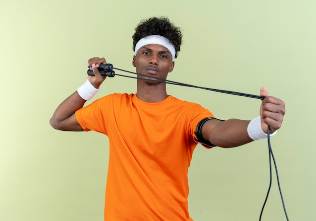 Op zoek naar een jonge afro-amerikaanse sportieve man met een hoofdband en een polsbandje met touwtjespringen
