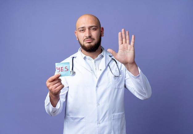 Op zoek naar een jonge kale mannelijke arts met een medisch gewaad en een stethoscoop die een papieren teken vasthoudt en een stopgebaar toont